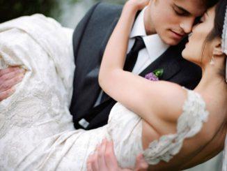 El novio carga a la novia para pasar el umbral de su casa